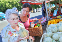 an elderly and a woman buying fruits